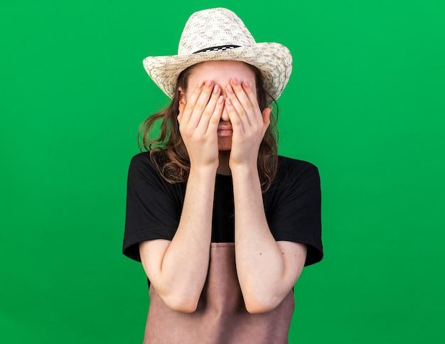 Il giovane giardiniere femminile che porta il cappello di giardinaggio ha coperto gli occhi con le mani isolate sul muro verde