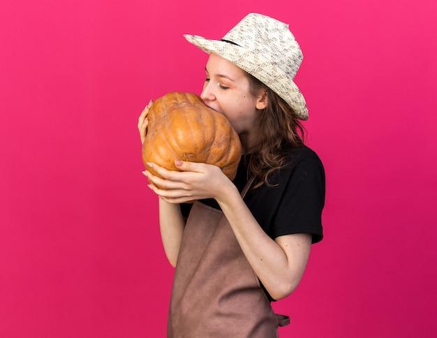Giovane giardiniere femminile che indossa cappello da giardinaggio che tiene morsi di zucca isolati su parete rosa