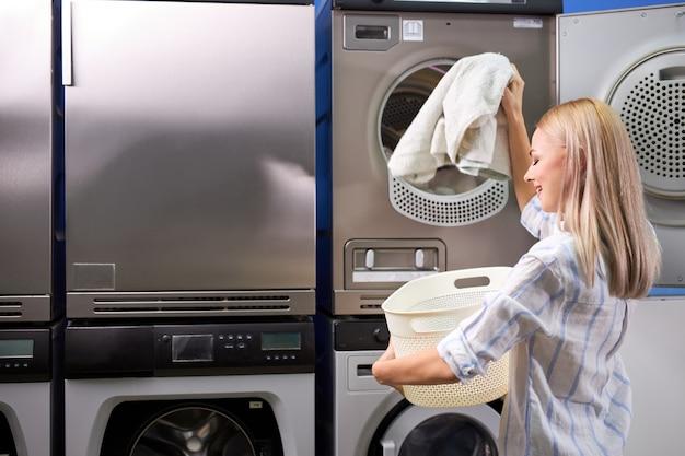 Giovane femmina che esce vestiti puliti dalla lavatrice, concetto di stile di vita della gente. pulizia, lavaggio