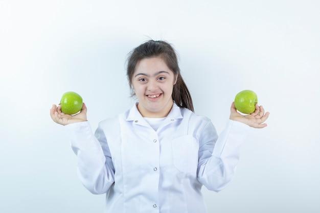 Giovane ragazza femminile in uniforme del medico che tiene i frutti della mela verde nelle mani.
