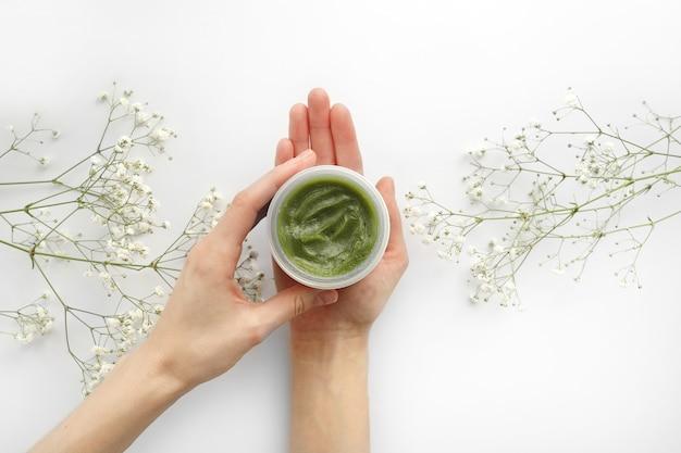 Le giovani mani femminili tengono un barattolo di crema naturale verde per il viso o il corpo. prodotti per la cura della pelle naturali organici e fiore su bianco. confezione di lozione o crema. concetto di bellezza cosmetica cura della pelle.