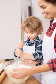 Giovane femmina e suo figlio in grembiuli sbattere le uova con la farina mentre si prepara la pasta per i biscotti fatti in casa a casa