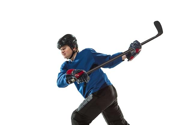 Giovane giocatrice di hockey con il bastone sul campo di ghiaccio e muro bianco