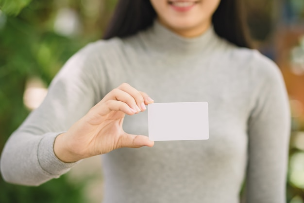 Giovane femmina che tiene la carta di credito in bianco, all'aperto