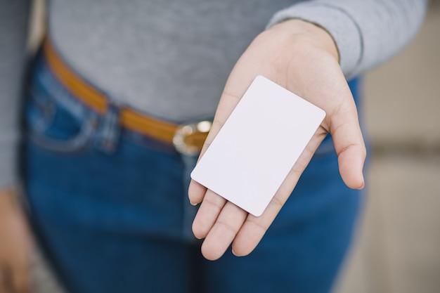 Giovane femmina che tiene carta di credito in bianco