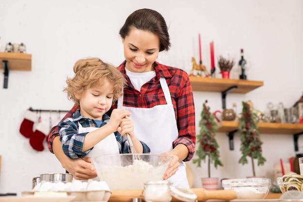 Giovane femmina che tiene ciotola con farina e uova mentre suo figlio li sbatte nel processo di preparazione dell'impasto per la pasticceria fatta in casa