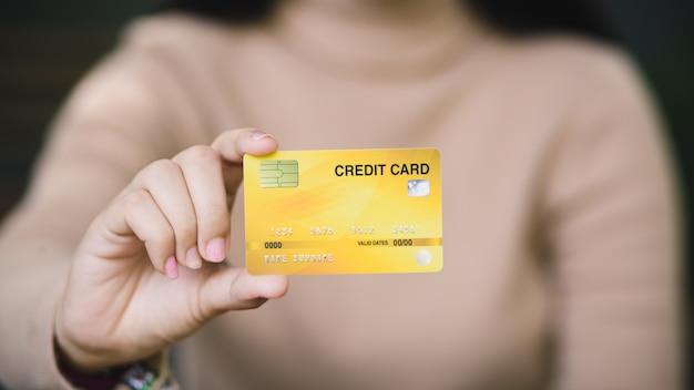 Giovane femmina che tiene la carta di credito
