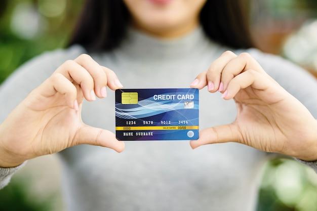 Giovane carta di credito femminile della tenuta