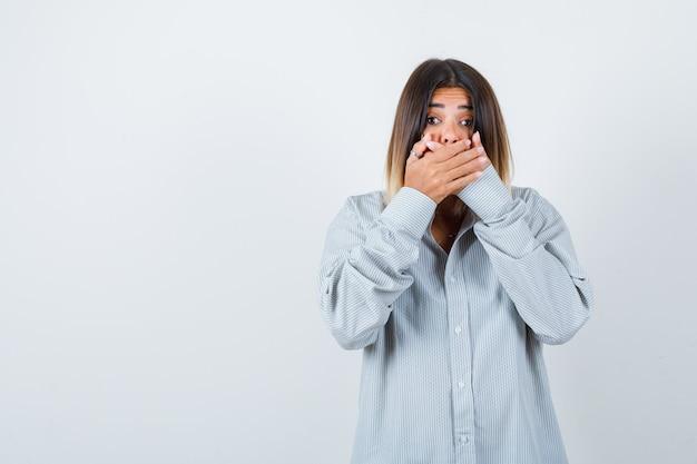 Giovane donna che si tiene per mano sulla bocca in camicia oversize e sembra spaventata, vista frontale.