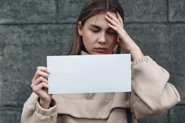 La giovane femmina tiene in mano un foglio di carta con la parola depressione.