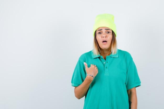 Giovane donna che tiene la mano sul petto in t-shirt polo, berretto e sembra sconcertata, vista frontale.