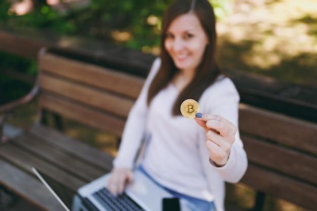 Giovane donna in abiti casual leggeri. donna seduta su una panchina con moneta bitcoin di colore dorato che lavora su un moderno computer portatile in strada all'aperto. mobile office online concetto di valuta virtuale