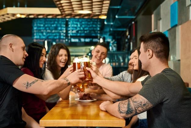 Giovani amici maschi e femmine che mantengono pinte con birra e tostatura in pub. felice compagnia seduta al tavolo, guardandosi l'un l'altro, ridendo e parlando al caffè. concetto di birreria e divertimento.