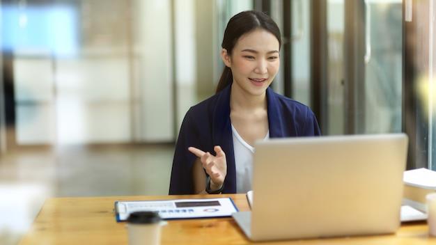 Giovane manager femminile che utilizza un dispositivo computer portatile mentre è seduto in un ufficio moderno, utilizzando un computer portatile per riunioni online con i colleghi