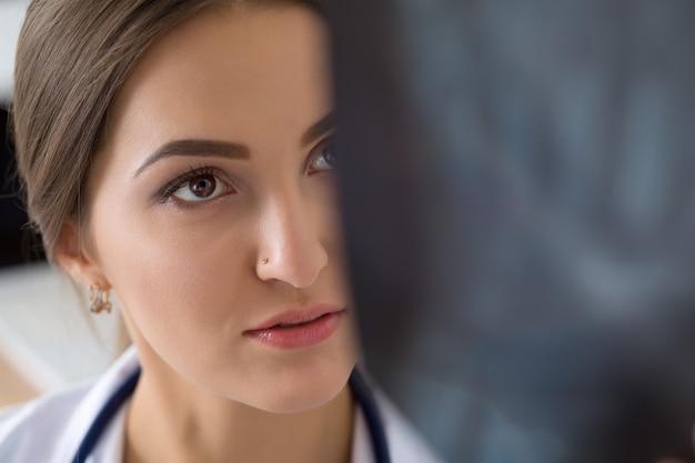 Giovane medico femminile o stagista guardando l'immagine dei polmoni x ray in piedi nel suo ufficio. radiologia, assistenza sanitaria, servizio medico o concetto di istruzione. primo colpo