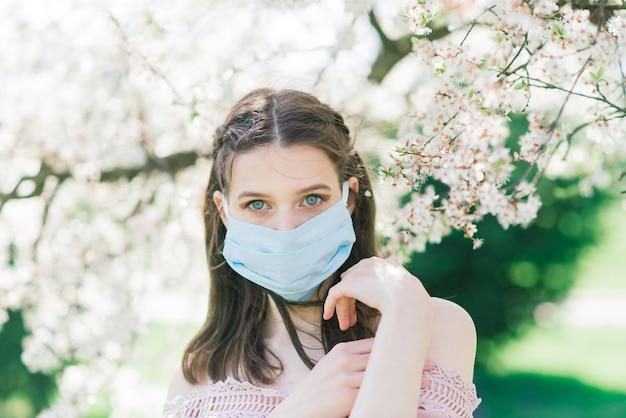 Una giovane donna con una maschera medica per evitare la diffusione del coronavirus nel parco tra alberi in fiore.