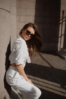 Giovane modello femminile con perfetto corpo sottile in occhiali da sole alla moda e pantaloni bianchi e camicia in posa sulla strada della città europea