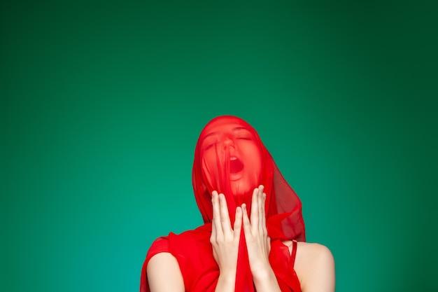Giovane modella femminile con velo rosso traslucido che copre il viso tenendo le mani vicino al collo e urlando o ansimando su sfondo verde