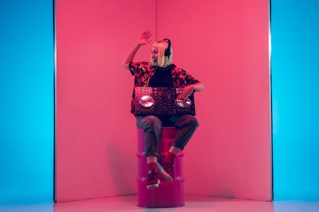Giovane musicista femminile in cuffie che si esibisce su sfondo blu-rosso alla luce al neon. concetto di musica, hobby, festival, intrattenimento, emozioni. ospite gioioso della festa, dj, ritratto dell'artista.
