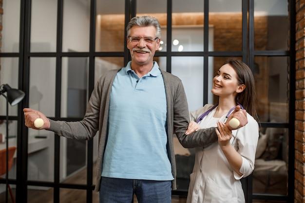 Giovane infermiera femminile che aiuta uomo anziano felice con l'esercizio con manubri.