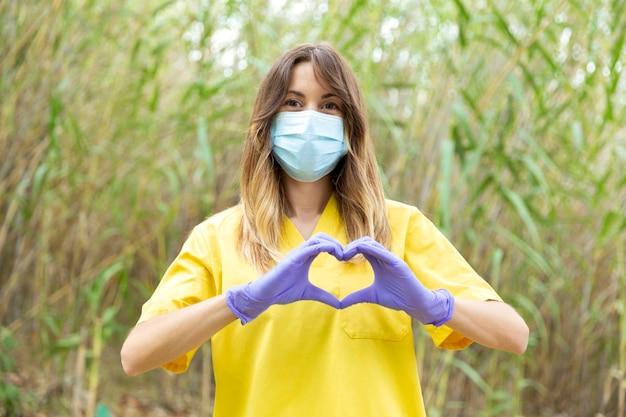 Giovane infermiera femminile nella mascherina medica uniforme