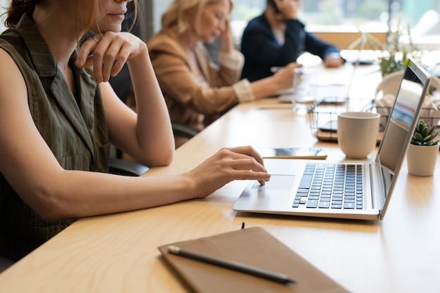 Giovane impiegato femminile prepara la presentazione del surf in rete mentre è seduto alla scrivania davanti al computer portatile contro i suoi colleghi