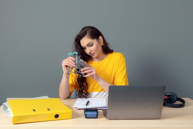 La giovane donna responsabile del negozio online si siede a una scrivania e lavora con un laptop e documenti, concetto di business online