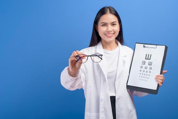 Un oculista femminile giovane con gli occhiali che tengono grafico dell'occhio sopra il blu, concetto di sanità