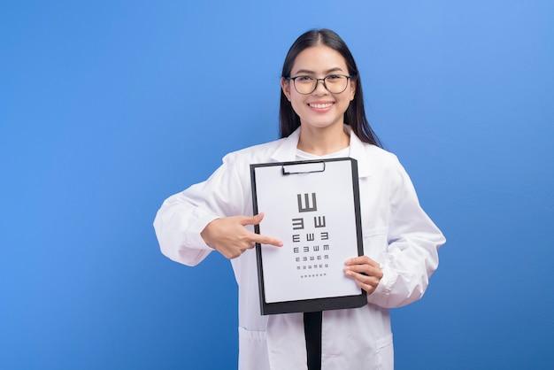 Un oculista femminile giovane con gli occhiali che tengono grafico dell'occhio sopra la parete blu, concetto di sanità