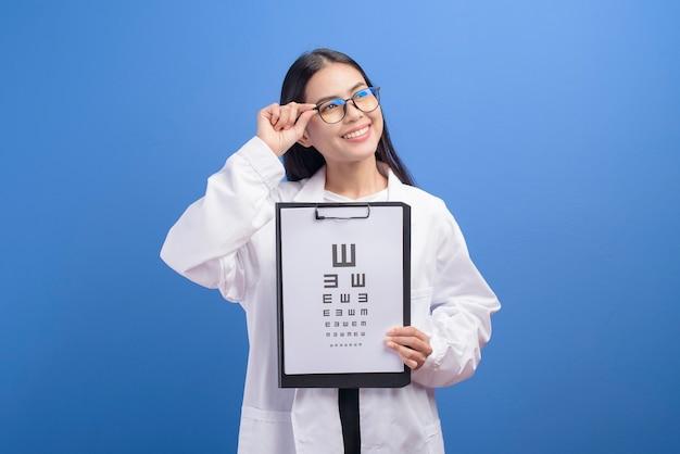 Un oculista femminile giovane con gli occhiali che tengono grafico dell'occhio sopra la parete blu
