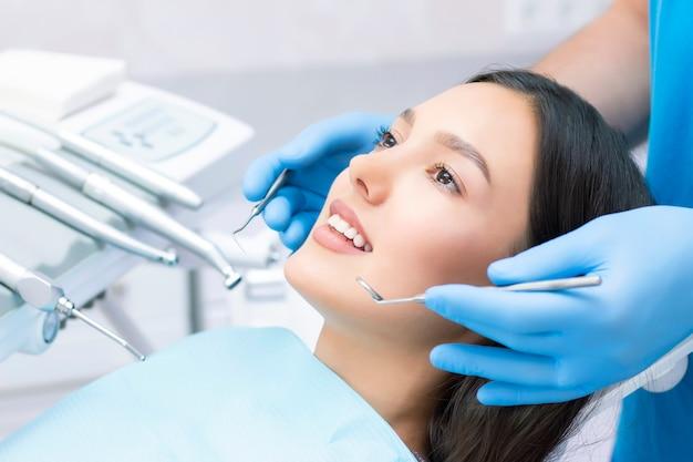 Giovane paziente femminile con un bel sorriso esaminando l'ispezione dentale presso la clinica del dentista