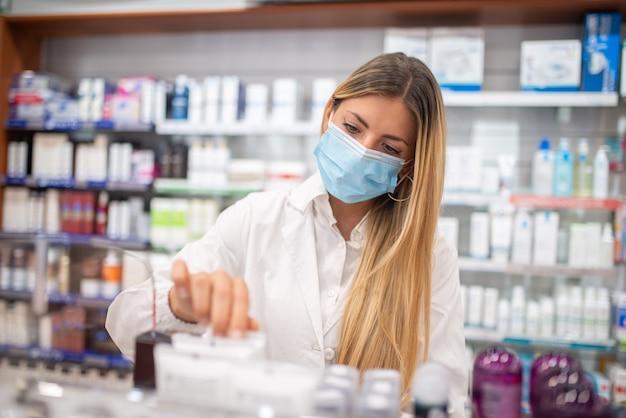 Giovane farmacista femminile che controlla l'inventario in una farmacia mentre indossa una maschera covid del coronavirus