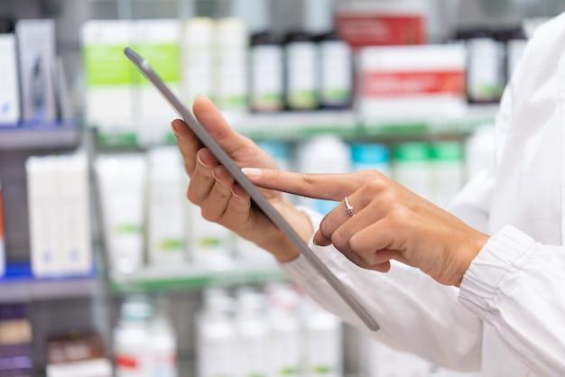 Giovane farmacista femminile che controlla l'inventario in una farmacia