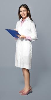 Giovane farmacista femminile con appunti su grigio