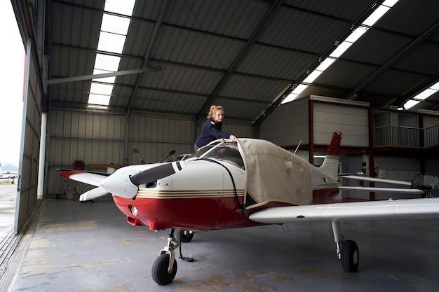 Giovane pilota femminile che copre aeromobili leggeri con copertura protettiva in hangar