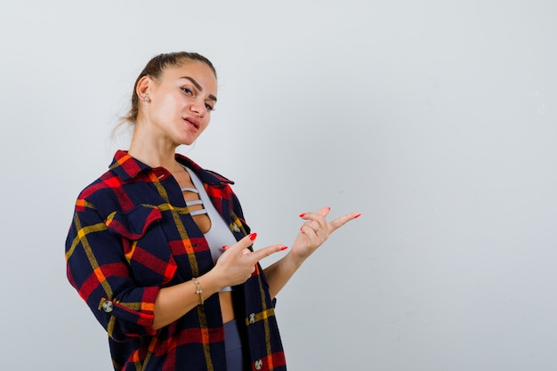 Giovane donna che indica il lato destro in top corto, camicia a scacchi e sembra sicura. vista frontale.