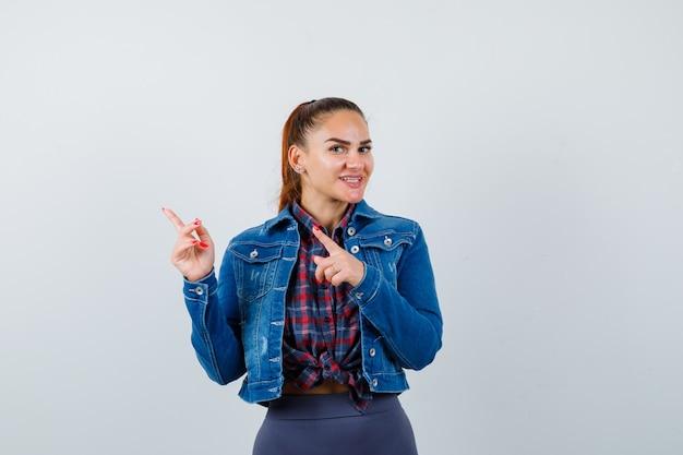 Giovane femmina che indica all'angolo superiore sinistro in camicia a scacchi, giacca, pantaloni e guardando felice, vista frontale.