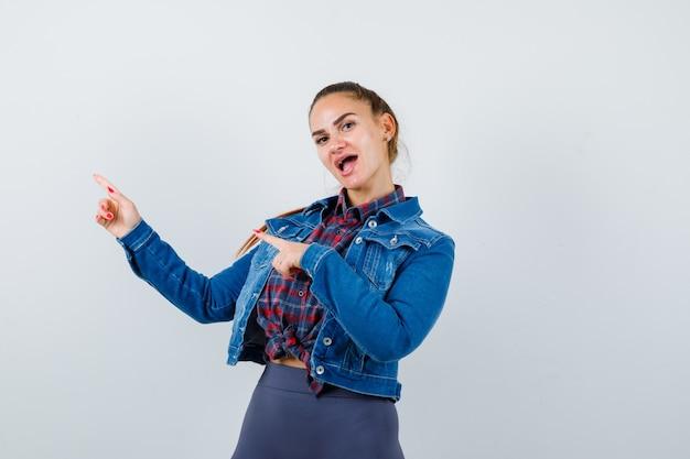 Giovane donna che punta all'angolo in alto a sinistra in camicia a scacchi, giacca, pantaloni e sguardo perplesso, vista frontale.