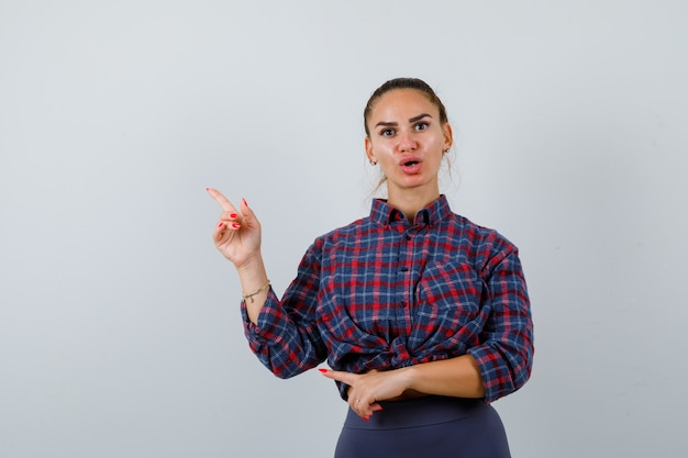 Giovane donna che punta all'angolo in alto a sinistra in camicia a scacchi, pantaloni e sembra perplessa, vista frontale.