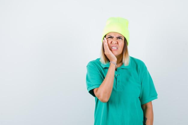 Giovane donna in t-shirt polo, berretto che soffre di mal di denti e sembra doloroso, vista frontale.