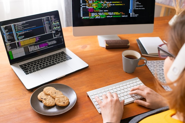 Giovane programmatore femminile seduto dal posto di lavoro a casa, prendendo il tè con i biscotti e digitando sulla tastiera del computer durante l'analisi dei dati