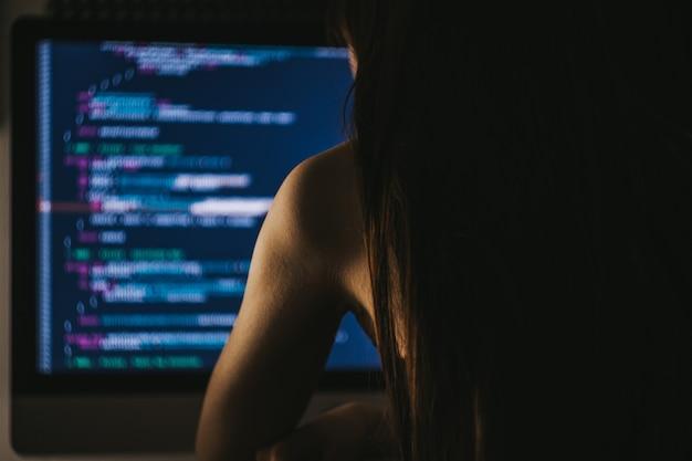 Il giovane programmatore femminile scrive il codice del programma su un computer