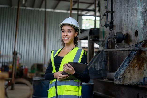 Giovane donna in uniforme protettiva ispezionando la macchina industriale e prendendo le note necessarie sulla tavoletta digitale presso l'impianto.