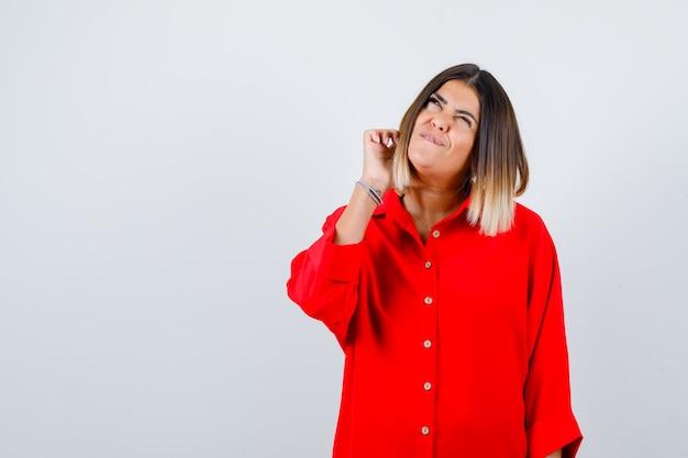 Giovane donna in camicia rossa oversize alzando lo sguardo e guardando premurosa, vista frontale.