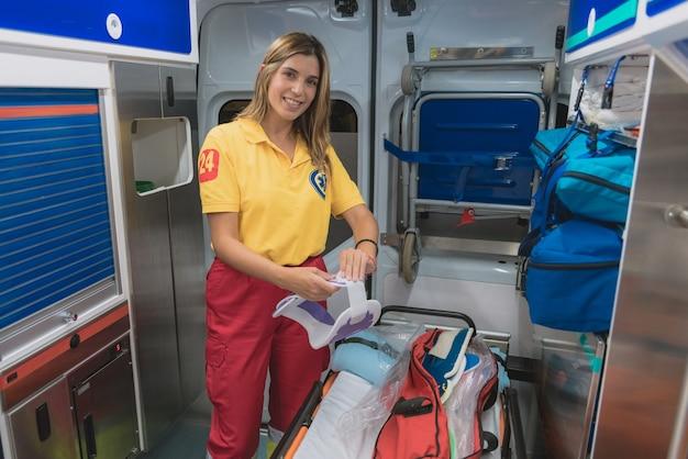Una giovane donna sanitaria prepara un'ambulanza per uscire e fare un servizio di emergenza