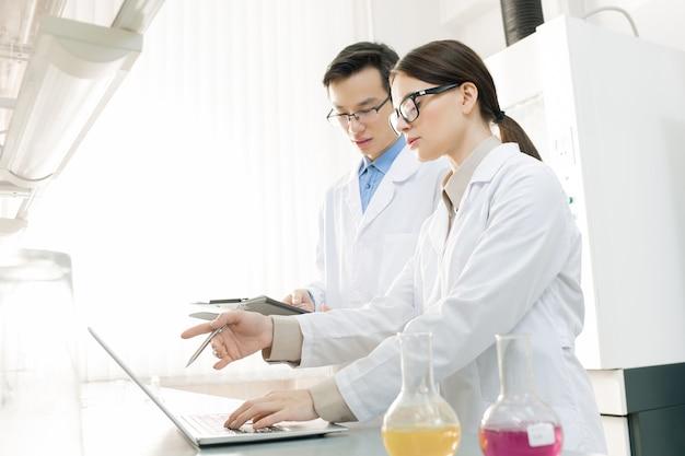 Giovane ricercatrice scientifica femminile che presenta il nuovo virus al suo collega e ne descrive le caratteristiche in laboratorio