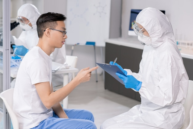 Giovane scienziato femminile in occhiali protettivi, maschera e tute che prendono appunti nel documento mentre consulta il ragazzo cinese in laboratorio