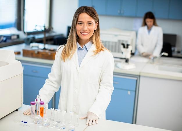 Giovane scienziato femminile in camice bianco in piedi nel laboratorio biomedico