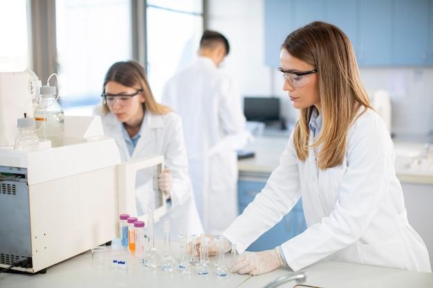 Giovani scienziati femminili in un camice bianco che mette la fiala con un campione per un'analisi