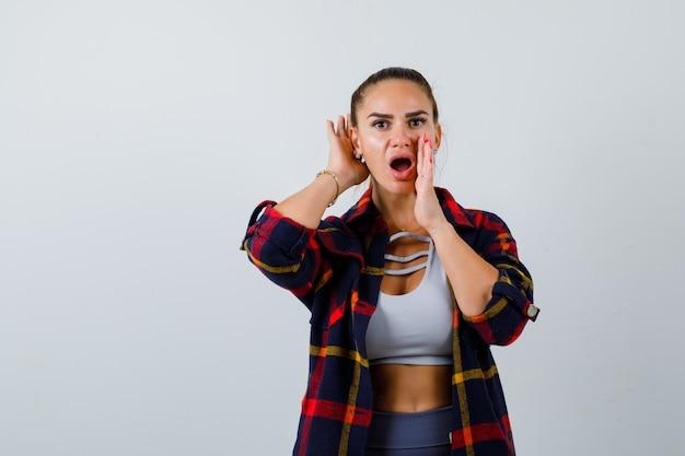 Giovane donna che grida qualcosa mentre con la mano dietro l'orecchio in crop top, camicia a scacchi, pantaloni e sembra seria. vista frontale.